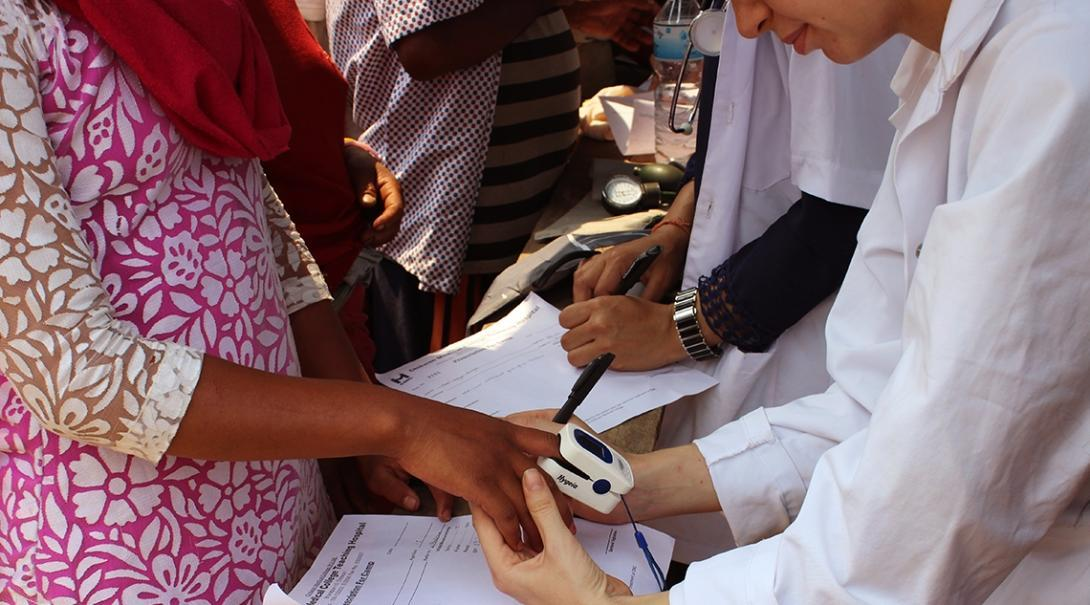 A local woman has her pulse and oxygen saturation levels measured by a Global Gap Year volunteer in Nepal.